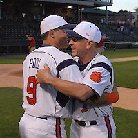 Head coach Jack Leggett (7) of the Clemson Tigers is congratulated by catcher Phil Pohl (9) after the Tigers defeated the Elon College Phoenix on March 21, 2012, at Fluor Field at the West End in Greenville, South Carolina. Clemson's 4-2 win gave Leggett his 1,200th career win. (Tom Priddy/Four Seam Images)