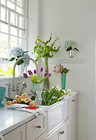 Cut flowers in the kitchen sink in the throes of being arranged into vases