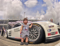 A young race fan stands next the the #59 Brumos Porsche before the Grand-Am race at Barber Motorsports Park, Birmingham, AL, Mach 31, 2012.  (Photo by Brian Cleary/www.bcpix.com)