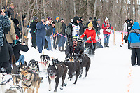 Tom Knolmayer and team run past spectators on the bike/ski trail near University Lake with an Iditarider in the basket and a handler during the Anchorage, Alaska ceremonial start on Saturday, March 7 during the 2020 Iditarod race. Photo © 2020 by Ed Bennett/Bennett Images LLC