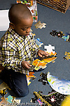 Educaton preschool 4-5 year olds boy working on floor puzzle vertical fitting two pieces together