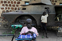 SOUTH SUDAN, Bahr al Ghazal region, Lakes State, town Rumbek , Dinka girl at old battle tank from war between SPLA and north sudanese army / SUED-SUDAN  Bahr el Ghazal region , Lakes State, Rumbek , Dinka Maedchen am Wrack eines nordsudanesischen Schuetzenpanzers aus dem Buergerkrieg mit dem Sudan an der Rumbek Secondary School
