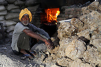 A man sits near a vat used for burning leather trimmings on the outskirts of the town of Kanpur. The leather is burnt, dried and then used as fertiliser and chicken feed. The area is now highly toxic having received the city's industrial waste for many years. Workers have little to no protection.