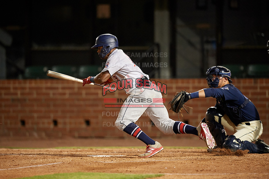 Jacksonville Jumbo Shrimp Stone Garrett (31) lays down a bunt in front of catcher Jack Kruger (10) during a Southern League game against the Mobile BayBears on May 7, 2019 at Hank Aaron Stadium in Mobile, Alabama.  Mobile defeated Jacksonville 2-0.  (Mike Janes/Four Seam Images)