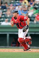 Catcher Jake Romanski (12) of the Greenville Drive runs to back up an infield play in a game against the Lexington Legends on Sunday, April 27, 2014, at Fluor Field at the West End in Greenville, South Carolina. Greenville won, 21-6. (Tom Priddy/Four Seam Images)
