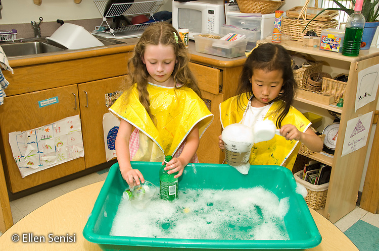 MR / College Park, Maryland.Center for Young Children, laboratory school within the College of Education at the University of Maryland. Full day developmental program of early childhood education for children of faculty, staff, and students at the university..Students (left: girl, 6; right: girl, 5, Korean-American) play at water table with cups and bottles..MR: Mar26 Jeo1.© Ellen B. Senisi