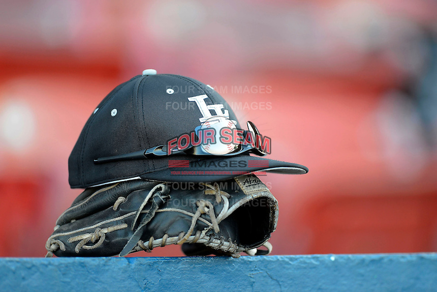 Long Island Blackbirds hat and glove on top of the dugout during a game against the Illinois State Redbirds at Chain of Lakes Stadium on March 8, 2013 in Winter Haven, Florida.  Illinois State defeated Long Island 6-4.  (Mike Janes/Four Seam Images)