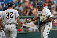 Michigan Wolverines designated hitter Jordan Nwogu (42) celebrates with his teammates after scoring during Game 1 of the NCAA College World Series against the Texas Tech Red Raiders on June 15, 2019 at TD Ameritrade Park in Omaha, Nebraska. Michigan defeated Texas Tech 5-3. (Andrew Woolley/Four Seam Images)