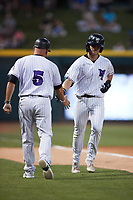 Travis Maniot (14) of the Winston-Salem Dash slaps hands with third abse coach Ryan Newman (5) after hitting a home run against the Greensboro Grasshoppers at Truist Stadium on June 17, 2021 in Winston-Salem, North Carolina. (Brian Westerholt/Four Seam Images)