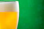 Close-up of beer in glass on green background