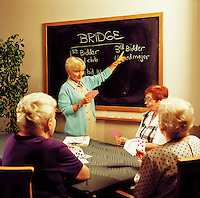 Senior women learning how to play bridge.