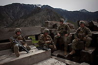 Marines rest in a lumber yard whilst on a mission in Nishigham village in Nuristan. They have recently disrupted the illegal logging trade that smuggles the wood across the border from Afghanistan causing some hostility in the area from local smugglers and gangsters. The mission was a joint patrol with the marines to the nearby village of Nishigham to re-supply an OP (Observation Post) that had been attacked the day before killing one ANA (Afghan National Army) soldier. The marines are acting as an ETT (Embedded Training Team) to mentor the ANA with the ultimate aim of leaving the country's security for the local Army to deal with.
