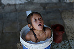 A Palestinian child bathes in a bucket who lives in an impoverished house in Khan Yunis in the southern Gaza Strip, on July 22, 2020. Photo by Osama Baba