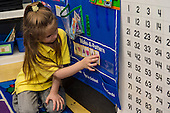 MR / Schenectady, NY. Zoller Elementary School (urban public school). Kindergarten inclusion classroom. Student (girl, 5) uses cards with different shapes on them to create a pattern during math learning center time. MR: Stu1. ID: AM-gKw. © Ellen B. Senisi.