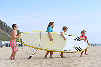 BNPS.co.uk (01202 558833)<br /> Pic: BNPS<br /> <br /> Pictured: Surfs up - (from left) Jack Bunn, 15, and Siblings, Charlotte, 13, Jasper, 10 and Lucas Reynaert, 7 head for the water at Boscombe in Dorset<br /> <br /> Weather input - Warm weather in Bournemouth<br /> <br /> People made the most of the late September sun at Bournemouth beach in Dorset today (Sunday).