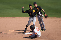 Pittsburgh Pirates second baseman Erik Gonzalez (2) throws to first base as Jahmai Jones (78) slides in during a Major League Spring Training game against the Baltimore Orioles on February 28, 2021 at Ed Smith Stadium in Sarasota, Florida.  Shortstop Kevin Newman (27) backs up the play.  (Mike Janes/Four Seam Images)