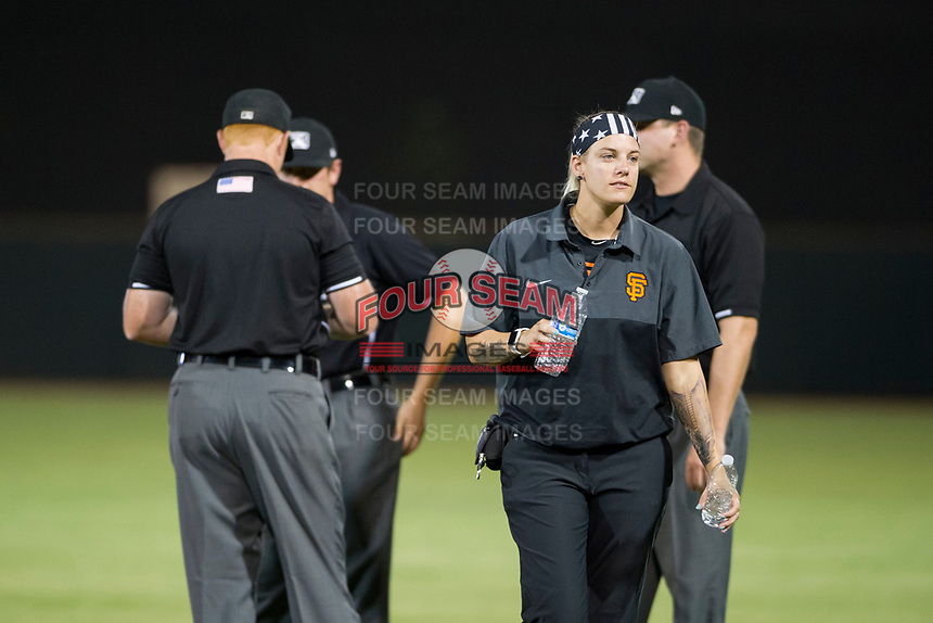 AZL Giants athletic trainer Charlene Wichman walks back to the dugout after offering water to Minor League umpires Jeff Hamann, Pete Talkington, and Ray Patchen during a game against the AZL Cubs on September 5, 2017 at Scottsdale Stadium in Scottsdale, Arizona. AZL Cubs defeated the AZL Giants 10-4 to take a 1-0 lead in the Arizona League Championship Series. (Zachary Lucy/Four Seam Images)