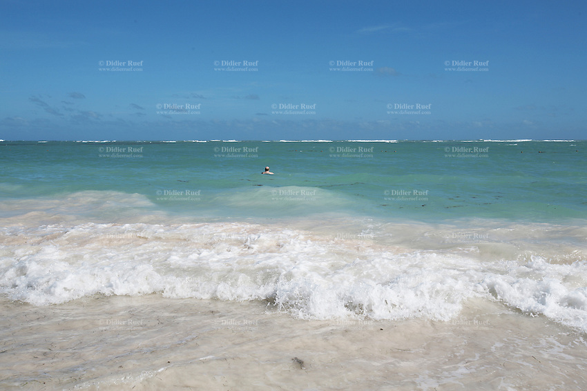 Dominican Republic. La Altagracia Province. Coastal resort of Punta Cana. Playa Bavaro. El Cortecito. A white bold man swims and enjoys alone the beauty of the sea. Blue sky. Punta Cana is well-known for its beaches where meet whites sands and warm turquoise water from the Atlantic Ocean. © 2006 Didier Ruef