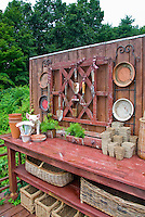 Garden potting bench and containers, pig statue ornament, baskets, hanging antique tools, pots, asparagus fern growing in old drawer, for charming place outdoors for gardening chores, Asparagus fern in drawers pot containers