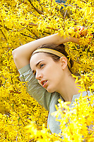 Beauty shot of young woman standing amoungst Forsythia flowers