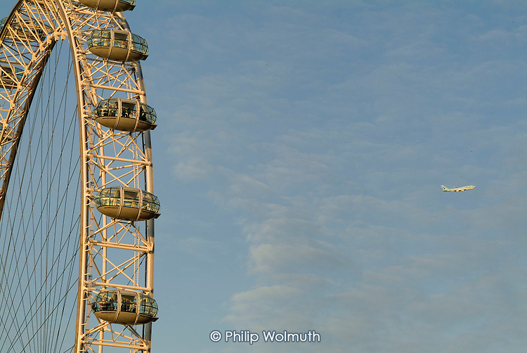 An aeroplane flies past the London Eye, on the South Bank of the River Thames