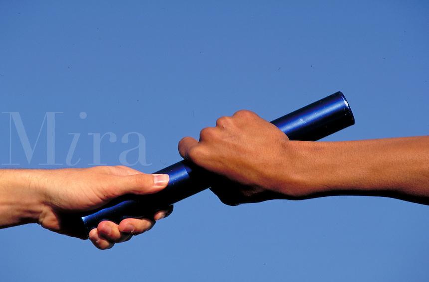 Hands pass baton in relay race. Relay racers.