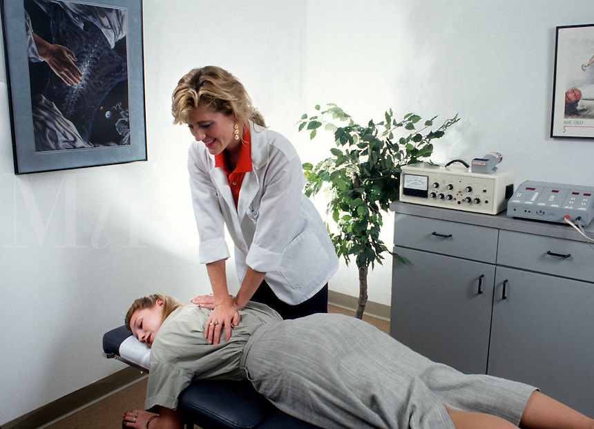 A female chiropractor performs an adjustment on a patient in her office.