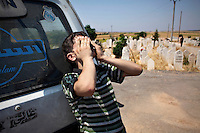A young boy cries for Omar Ismail Abdul Rahman (30) who died fighting for the FSA in Salaheddin, Aleppo, at his funeral in Tal Rifaat. Omar, a farm boy from Northern Syria took up arms against the government and was killed fighting on the front lines of Saluheddin in Aleppo. He was buried in his hometown near the fields he worked in before the revolution.