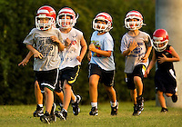 Each fall football season, youths across the United States pull on helmets and strap on pads to play American football, one of the country's most popular sports. The Pop Warner football league has been helping youngsters play the sport since 1929. Photo is part of a series of images documenting one team of North Carolina boys learning and playing the sport in Cornelius, NC in fall 2009. They're playing on the Lake Norman Giants.