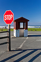 Stop sign and ranger kiosk at the entrance to Pomponio State Beach, California.