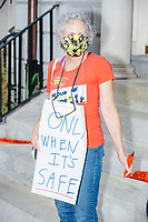 """A demonstrator holds a sign reading """"Only When It's Safe"""" as people gathered outside the Massachusetts State House for a protest organized by the Massachusetts Teachers Association against current school reopening plans during the ongoing Coronavirus (COVID-19) global pandemic in Boston, Massachusetts, on Wed., Aug. 19, 2020. The teachers' union, alongside two other Massachusetts teachers' unions, organized the event as part of a mass day of action demanding that the school year starts with remote learning and switch to in-person learning only when health and safety standards can be guaranteed."""