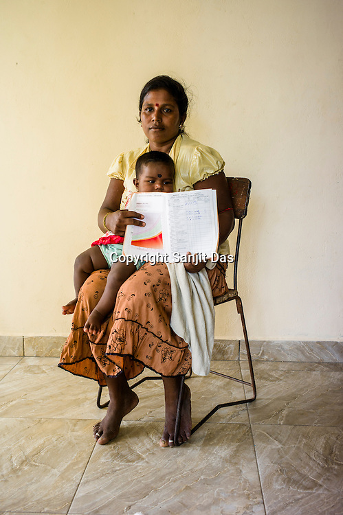 A Sri Lankan woman poses for a photo with her child and the CHDR- Child Health Development Record Card (immunization/vaccination card) in the Ministry of Health office in Tharmapuram Village in Kilonochchi, Sri Lanka.  Photo: Sanjit Das/Panos