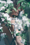 Romantic sensual portrait of a beautiful nude young woman behind white flowers of apple blossom outdoors in spring in soft green colors Image © MaximImages, License at https://www.maximimages.com
