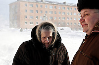 Elderly people walk by a half-abandoned housing block in Teriberka, a former prosperous fish-processing community. Teriberka's population shrunk from about 14,000, at its height, to just over a 1,000 after the fishing industry collapsed. However one of the world's largest known natural gas reserves, the Shtokman gas field, was discovered off its shores and promises to bring new life to the area. /Felix Features