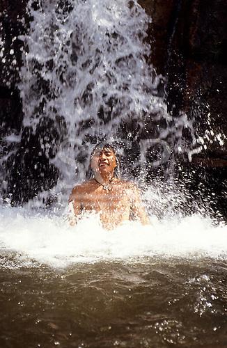 Roraima state, Brazil. A young Yanomami Indian man enjoying bathing in a waterfall.