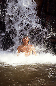 Roraima state, Brazil. A young Yanomami Indian man enjoying bathing in a waterfall.