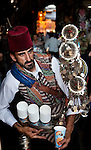 A man dressed in traditional clothes prepares to pour a glass of tamarind juice from a intricately decorated metal pitcher at the Al Hamidiyah Souq in the Old City.