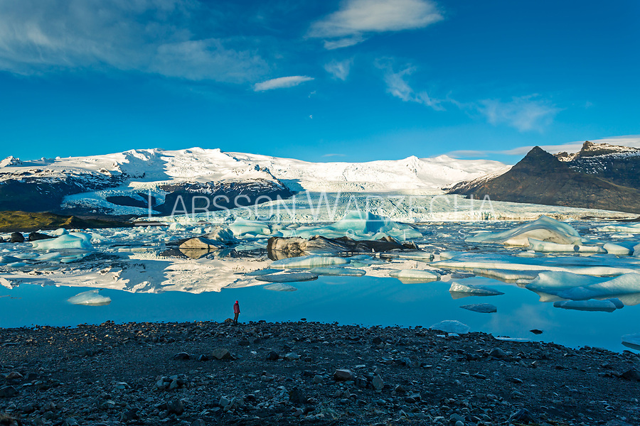 Woman walking in front of glacial lake with glacier and mountains in the background, Iceland