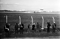 Le  1er vol d'essai du Concorde-<br /> Aérogare Blagnac ,Toulouse, France,<br />  2 mars 1969<br /> <br /> au 1er plan groupe de personnes (vue de dos) regarde l'avion derrière les clôtures, gendarmes, un petit garçon se retourne main levée