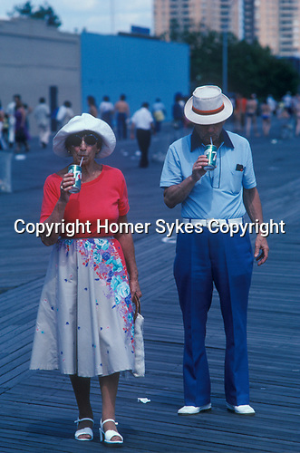 Coney Island New Jersey USA Circa 1970. Senior couple  in sun glasses on vacation drinking a can 7 UP through a straw. Broadwalk.