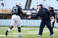 CHAPEL HILL, NC - OCTOBER 10: North Carolina Offensive Line Coach Stacey Searels low-fives Ed Montilus #63 during a game between Virginia Tech and North Carolina at Kenan Memorial Stadium on October 10, 2020 in Chapel Hill, North Carolina.