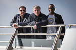 © Joel Goodman - 07973 332324 . NO SYNDICATION PERMITTED . 19/03/2015 . Salford Quays , UK . Shaun Ryder , Mark Berry ( Bez ) and Paul Leveridge ( Kermit ) . Black Grape photocall at The Green , Salford Quays , Greater Manchester . Black Grape are reforming for a Madchester charity gig along with other local bands , to raise awareness for Bez's Reality Party and anti-fracking . Photo credit : Joel Goodman