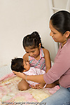 newborn baby girl one month old  Mexican American  held by mother with older sister age 3 vertical