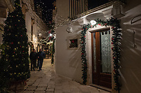 """Italy. Apulia Region. Locorotondo. Christmas decoration. A group of elderly men holds arms and walks together in the tiny streets at night time. Locorotondo is a town and comune with a population of about 14,000. The city is known for its circular structure which is now a historical center, from which derives its name, which means """"Round place"""". Apulia (Puglia) is a region in Southern Italy. 5.12.18  © 2018 Didier Ruef"""