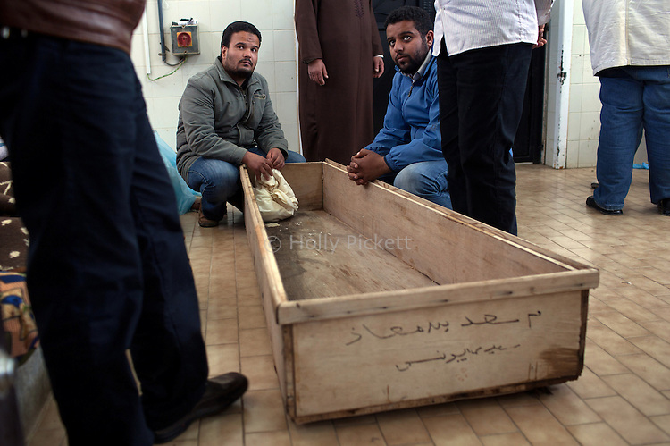 Men waited next to a coffin at the hospital morgue in Benghazi, Libya, March 20, 2011. Family members prepared those killed during fighting between opposition rebels and loyalist forces of Col. Muammar Qaddafi for burial. The main hospital in Benghazi reported around 50 dead fighters and civilians the previous day and at least 35 on Sunday.