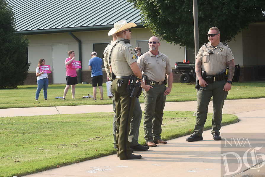 Benton County deputies and sign carriers stand Tuesday July 20 2021 at the meeting entrance at Northwest Arkansas Community College.<br />(NWA Democrat-Gazette/Flip Putthoff)