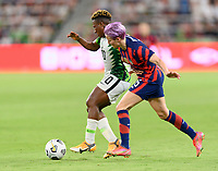 AUSTIN, TX - JUNE 16: Megan Rapinoe #15 of the United States and Rita Chikwelu #10 of Nigeria battle for control of the ball during a game between Nigeria and USWNT at Q2 Stadium on June 16, 2021 in Austin, Texas.