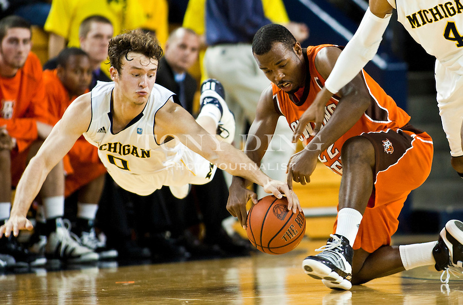 Michigan guard Zack Novak, left, dives to win a loose ball from Bowling Green guard Dee Brown, center, in the second half of an NCAA college basketball game, Thursday, Nov. 18, 2010, in Ann Arbor. Michigan won 69-50. (AP Photo/Tony Ding)
