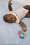 5 month old baby boy African American on back vertical rolling to reach for and grasp  toy