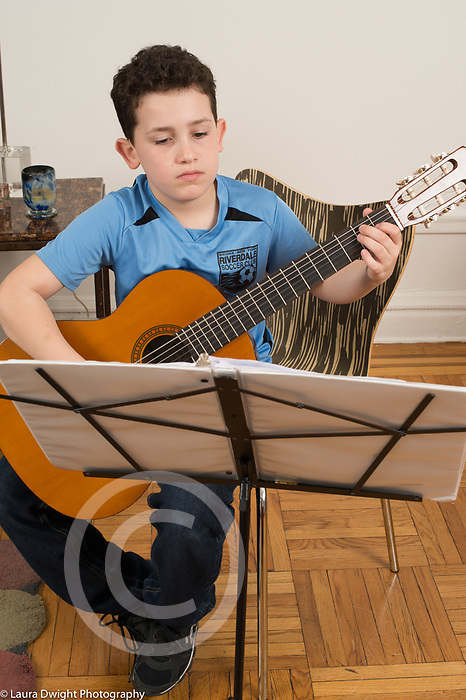 10 year old boy at home practicing guitar